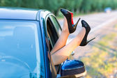 Woman's legs in highheel shoes out of a car window — Stock Photo
