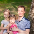 Happy father with daughters playing in the park — Stock Photo #27520087
