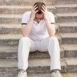 Frustrated stressed young man sitting on stairs — Stock Photo #27526101