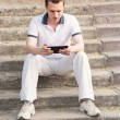 Young man sitting on a stairs with tablet pc — Stock Photo #27526111