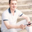 Young man sitting on a stairs with tablet pc — Stock Photo #27526127