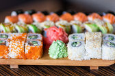 Sushi rolls served on a wooden plate — Stock Photo