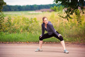 Runner woman stretching in nature outdoor — Stock Photo