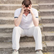 Frustrated stressed young man sitting on stairs — Stock Photo