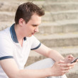 Young man sitting on a stairs with tablet pc — Stock Photo #29526131