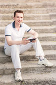 Young man sitting on a stairs with tablet pc — Stock Photo