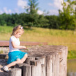 Cute little girl sitting near the lake — Stock Photo