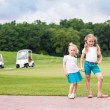 Cute little gilrs on the golf course — Stock Photo