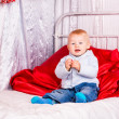 Cute baby boy on a bed playing — Stock Photo