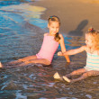 Stock Photo: Two adorable kids playing in the sea on a beach