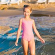 Adorable little girl playing in the sea on a beach — Stock Photo #31727171