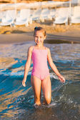 Adorable little girl playing in the sea on a beach — Stock Photo