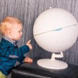 Adorable curious baby boy with a globe — Stock Photo
