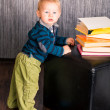 Adorable baby boy with a pile of books — Foto de Stock
