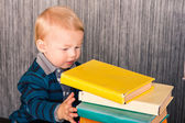 Adorable baby boy with a pile of books — Stock Photo