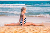 Beautiful little girl excercising on the beach — Stockfoto