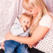 Stock Photo: Beautiful happy mother hugging baby on a bed