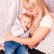 Beautiful happy mother hugging baby on a bed — Stock Photo