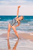 Vackra lilla tjej utövar på stranden — Stockfoto