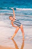 Belle petite fille excercising sur la plage — Photo