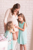 Beautiful pregnant woman with two daughters — 图库照片