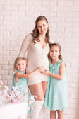 Beautiful pregnant woman with two daughters — Stock Photo