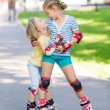 Two little girls rollerskating in the park — Stock Photo #50151137