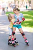 Two little girls rollerskating in the park — Stock Photo