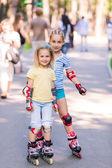Dwie dziewczynki rollerskating w parku — Zdjęcie stockowe