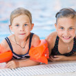 Two cute little girls in swimming pool — Stock Photo #50303675