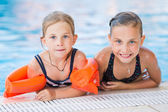 Two cute little girls in swimming pool — Stock Photo