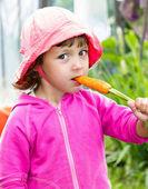Little girl eating fresh carrot — Stock Photo