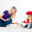 Stock Photo: Pretty young mother and daughter drawing