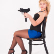 Pretty girl with gun on chair — Stock Photo