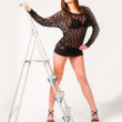 Pretty brunette girl standing at ladder — Lizenzfreies Foto