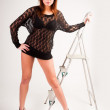 Pretty brunette girl standing at ladder — Stock Photo