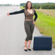 Woman with suitcase on road — Stock Photo
