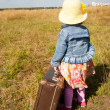 Lonely girl with suitcase. Back view — Stock Photo
