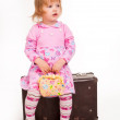 Portrait of adorable young girl on old suitcase — Stock Photo