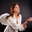 Young sexy woman with angel wings calling - Stock Photo