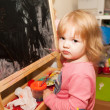 Girl paints at the easel — Stock Photo