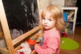 Chica pinturas en el caballete — Foto de Stock