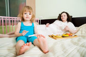 Pregnant mother with daughter in bedroom — Stock Photo