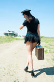 Sexy police woman going with old suitcase — Stock Photo