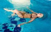 Attraktiva flicka med mössa i poolen — Stockfoto