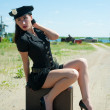 Sexy police woman sitting on old suitcase — Stock Photo