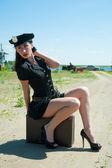 Sexy policji kobieta siedzi na stare walizki — Zdjęcie stockowe