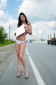 Sexy nude woman holding blank banner on road — Stock Photo