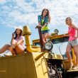 Young attractive women on old big tractor — Stockfoto