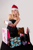 Blond woman with shopping bags and gift — Stockfoto
